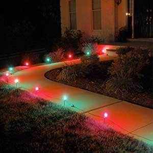 Red and green pathway lights from Home Depot leading up to the front door of a house photo