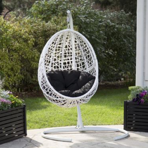 White wicker hanging egg chair with a black cushion inside. photo