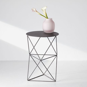 Black side table with geometric steel base. photo