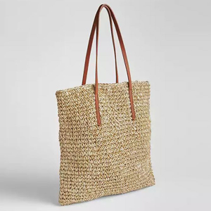 Metallic straw tote with long brown handles. photo