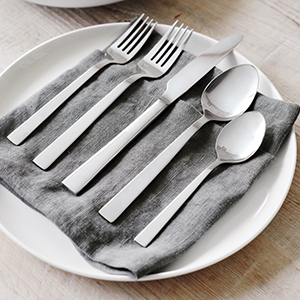 Set of two forks, one knife, and two spoons in silver arranged on a gray napkin on a white plate photo