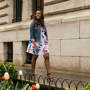 Nyakio Grieco wearing floral dress and denim jacket photo