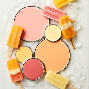 Orange, coral, and yellow paint lids next to popsicles photo