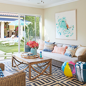 Sunroom featuring wicker couch, wood coffee table, and geometric area rug photo