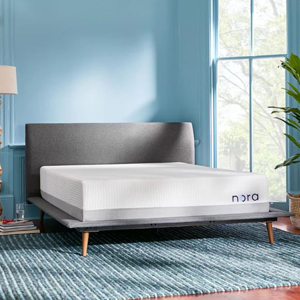 Nora mattress on gray bed frame with wooden legs with a light blue wall color. photo