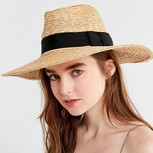 Woman wearing a straw Joanna hat with a black band around it. photo