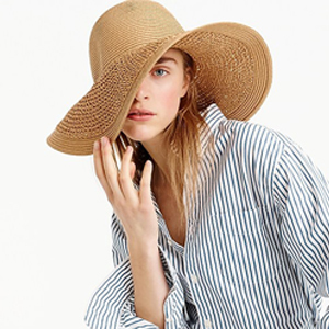 A woman wearing an oversized floppy straw hat with a striped button-down shirt. photo