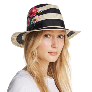 A woman wearing a straw hat with black stripes and floral embroidery on the side. photo