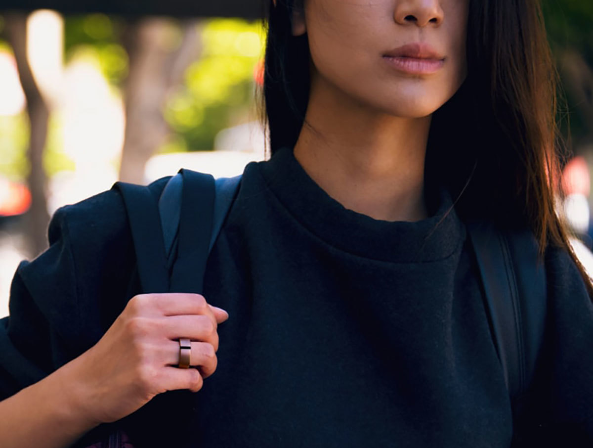 Women wearing rose gold Motive Ring while carrying a backpack photo