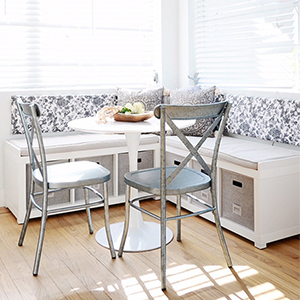 Breakfast nook with white storage bench and metal dining chairs photo