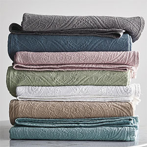 Home Depot stack of coverlets in green, blue, pink, white, and tan photo