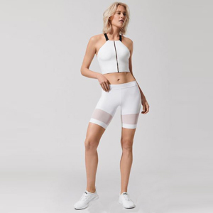 Woman wearing white bike shorts with a mesh panel at the bottom of each leg. photo