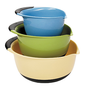 Three OXO mixing bowls in blue, green, and light yellow stacked on top of one another photo
