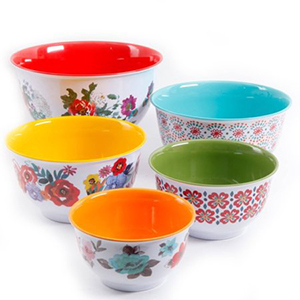 Assortment of five mixing bowls with floral patterned exteriors and colorful interiors including: red, orange, yellow, blue, and green. photo