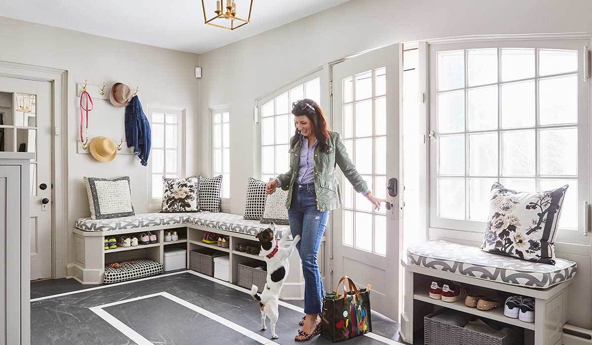 Interior designer Amanda Reynal standing in gray and white mudroom with her dog.