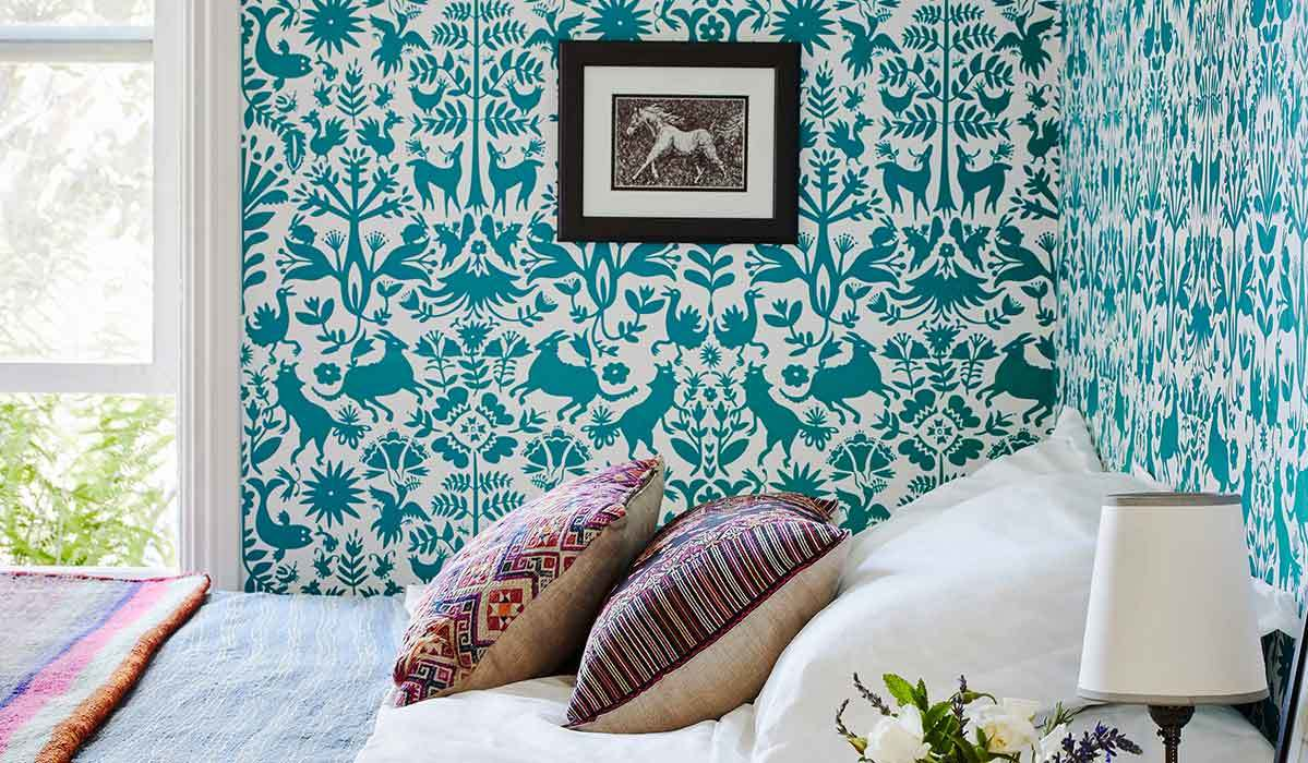 Bedroom with teal wallpaper, horse art, and tribal-print pillows on bed