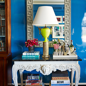 A room with bright blue walls, a white table, and decor on top. photo