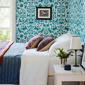 A room with bold teal and white patterned walls. photo