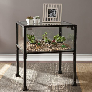 Terrarium side table in a living room with rocks and plants inside. photo