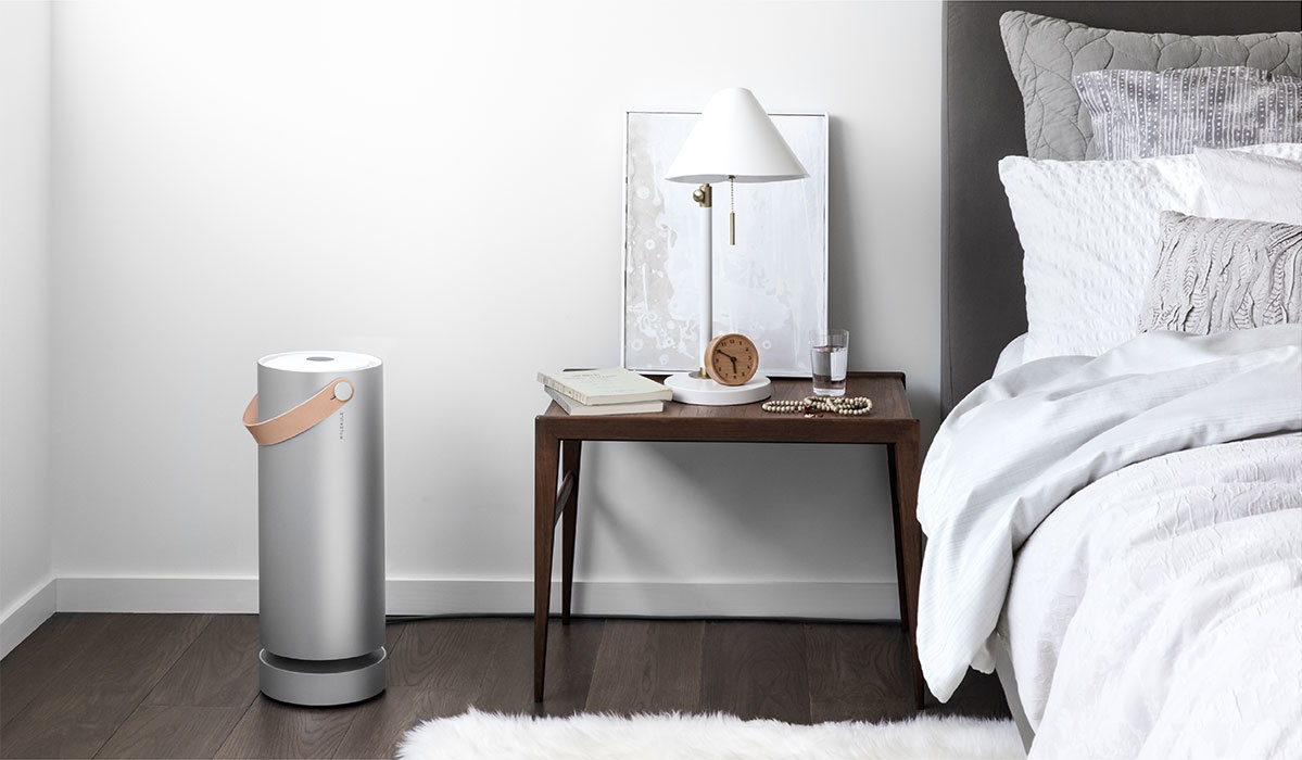 Molekule air purifier next to bedside table in a bedroom setting