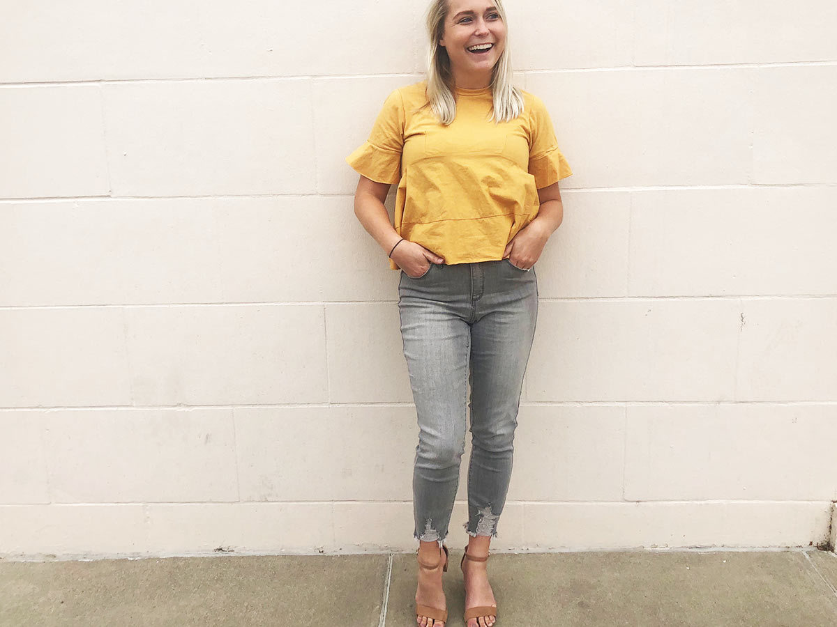Shop editor Lauren wearing gray-wash Target jeans with nude heels and a yellow blouse. photo