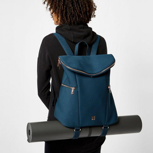 Woman carrying a blue backpack with a yoga mat. photo