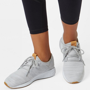 A woman wearing a pair of gray New Balance shoes. photo