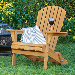 Natural wood Adirondack chair with a striped throw blanket draped on one side. photo