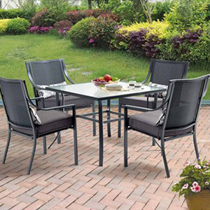 Charcoal gray dining set with table and four chairs sitting on patio pavers. photo