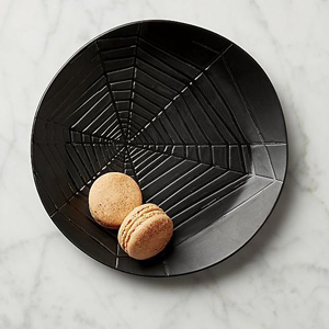 Black salad plate with a spiderweb design etched into it. photo