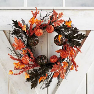 Wreath with yellow, red, and black leaves, berries, sticks, and pumpkins on it. photo