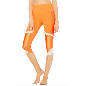 Orange cropped leggings with white stripes on the side. photo