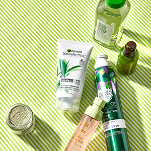 Green tea skin care products on green and cream striped background. photo