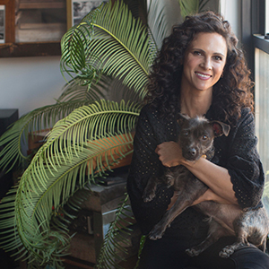 Gita Bass photographed with her dog and a plant in the background. photo