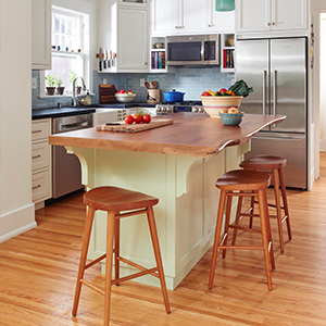 Photo of a kitchen island with natural wood countertop. photo
