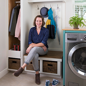 Photo of a woman sitting on a bench in her laundry room. photo