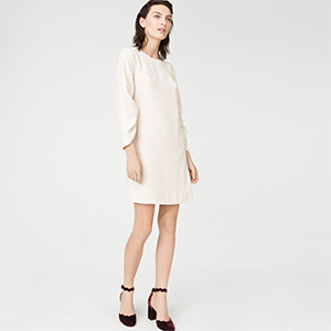 Model wearing a white long-sleeve dress paired with black block heels photo