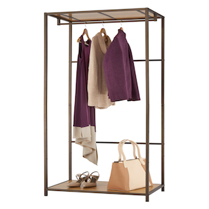 Bamboo garment rack with three clothing items hanging and a purse and shoes sitting on the lower shelf. photo