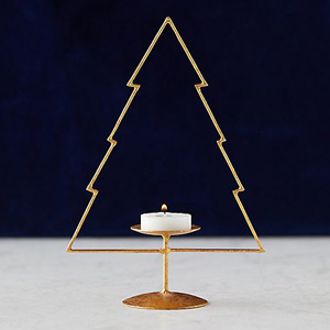 Gold candleholder in the shape of a christmas tree holding a small candle from Shop Terrain. photo