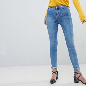 High-rise skinny jeans paired with a yellow long-sleeve shirt and heels. photo