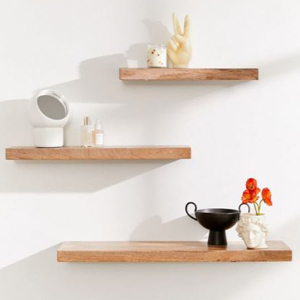 Wood floating shelves in different sizes with small decor on each. photo