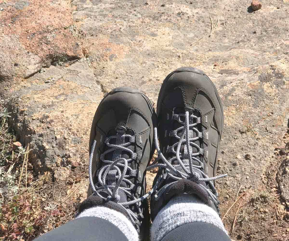 Carly wearing her Merrell hiking boots while climbing a mountain. photo