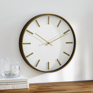 Large brass wall clock with a white face hanging on the wall over a wooden table. photo