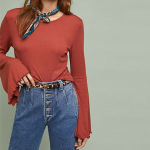 Bell-sleeve top with ruffles at the edges in the color medium orange paired with jeans and a tie scarf. photo