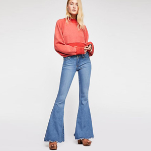 Denim flare jeans with distressed edges paired with red long sleeve top. photo