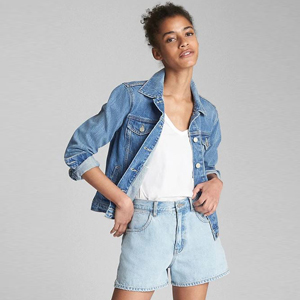 Denim jacket with patchwork on the back in the shape of the United States paired with a white V-neck. photo