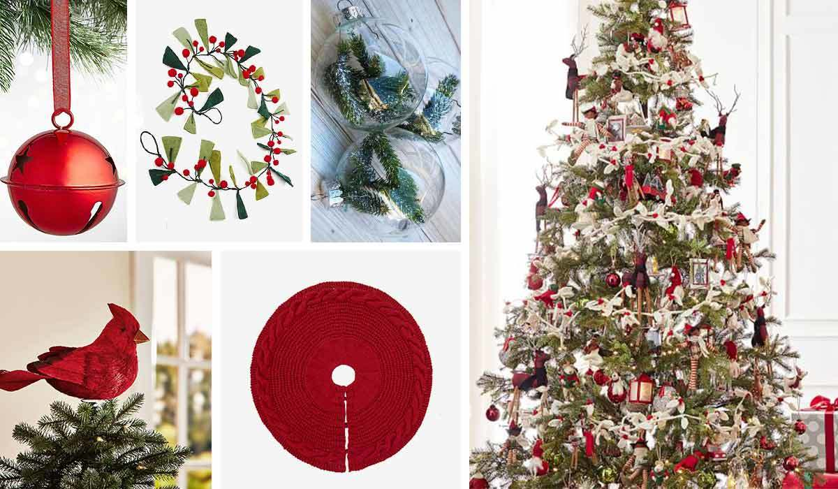 Red tree skirt with cardinal tree topper, red and green ornaments, and bell ornament photo