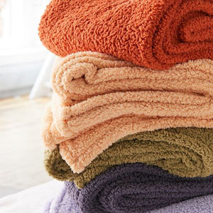 Fleece throw blankets folded in various colors. photo
