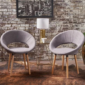 Two dining chairs with gray upholstery and wooden legs. photo