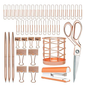 Rose gold office supplies including, paper clips, pens, scissors, a stapler, a pen holder, and clips. photo